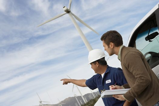 Male engineers examining wind turbines by car at wind farm