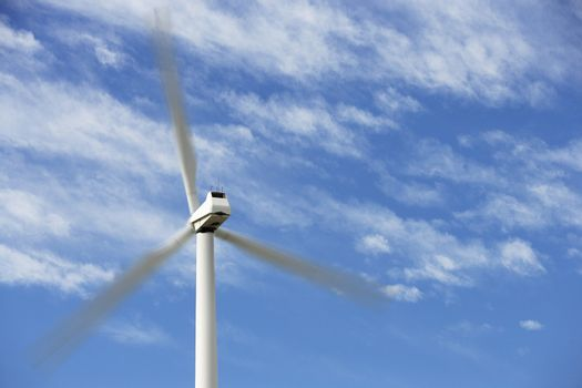 Wind turbine in motion against cloudy sky at wind farm