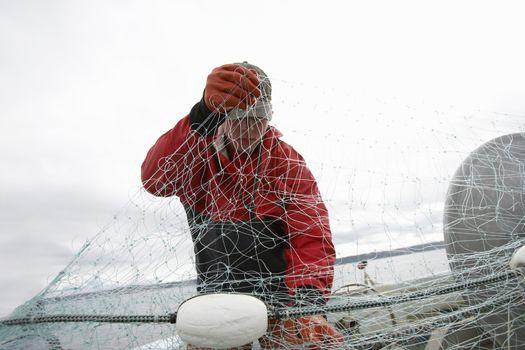 Fisherman detangling fishing net on boat