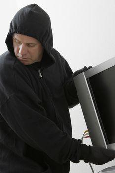 Burglar in black sweatshirt stealing television set from house