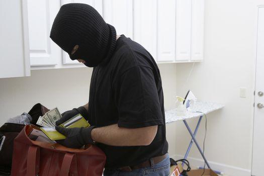 Burglar in balaclava stealing money from wallet