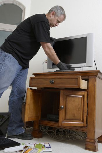 Male burglar stealing television from house