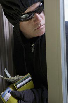 Closeup of a male burglar stealing money from wallet