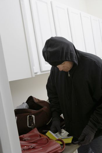 Burglar stealing money from wallet in a house