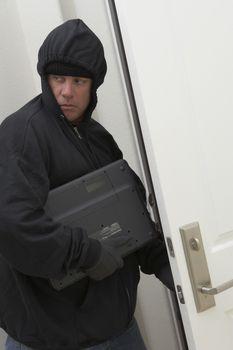 Burglar stealing laptop from house