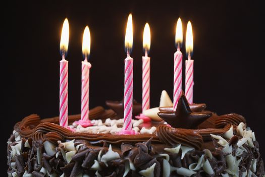 Closeup of a birthday cake with lit candles