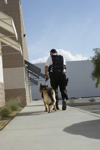 Rear view of a security guard with dog on patrol
