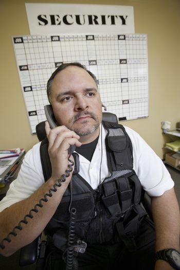 Caucasian security guard using telephone in office