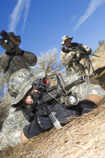 Military soldiers aiming machine guns ready for combat