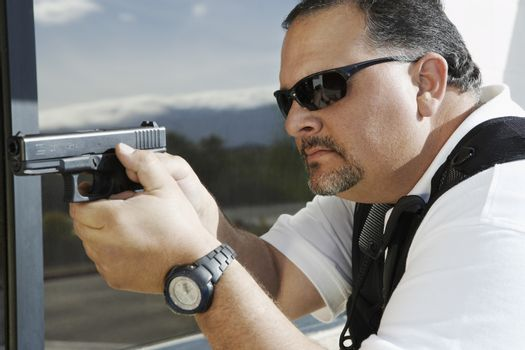 Side view of a security guard aiming with gun