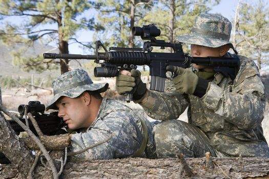 US army soldiers aim with rifle while leaning on log