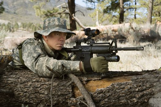US army solider aims machine gun while leaning on log