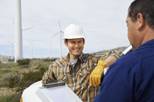Happy engineer with colleague near wind turbines at wind farm