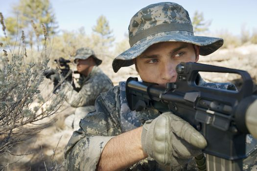 Two US army soldiers with weapons on battle field