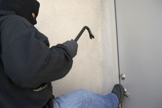 Burglar with crowbar kicking the door of house