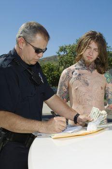 Male police officer writing ticket for arrested drug dealer