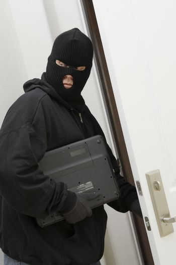 Thief in balaclava stealing laptop from house