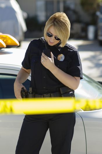 Female police officer using two-way radio by car behind caution tape
