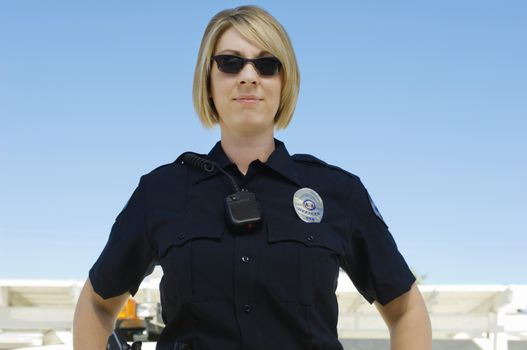 Female police officer with sunglasses against clear sky