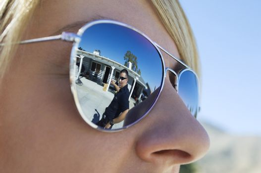 Closeup of a police officer's reflection on sunglasses of coworker