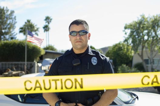 Police officer standing behind police tape at crime scene