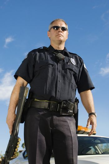 Low angle view of a police officer holding weapon against sky