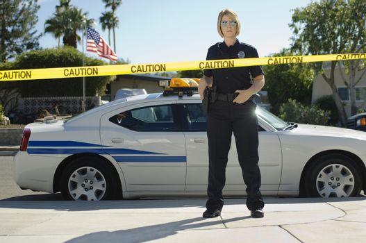 Full length of a female police officer standing by car behind caution tape