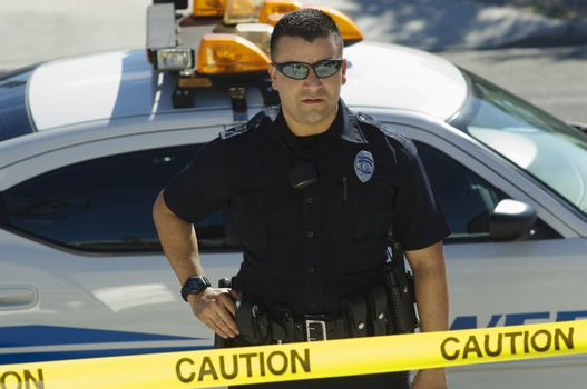 Male police officer standing by car behind caution tape