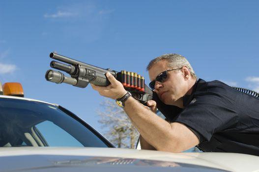 Caucasian male police officer aiming shotgun