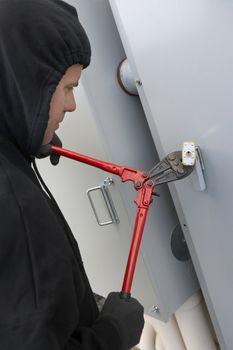 Thief breaking the door lock with cutter