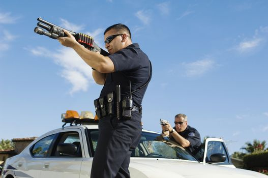 Side view of two police officers defending with guns against sky