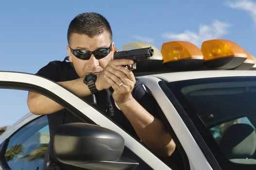 Police officer aiming with handgun by patrol car