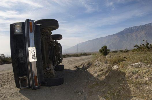 Rolled over car at roadside in desert