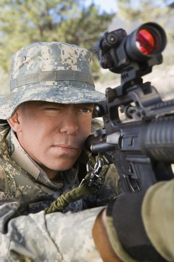 Closeup of US army solider aiming to shoot with machine gun