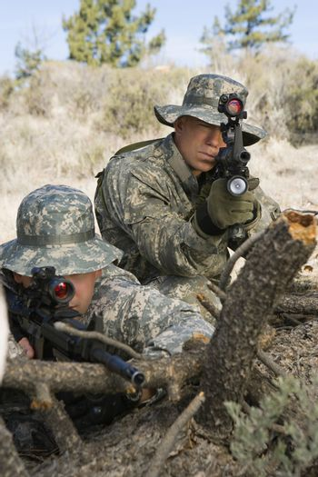 Two armed soldiers with machine guns leaning on log