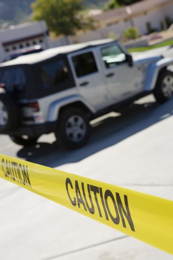 Police jeep behind yellow caution tape at crime scene