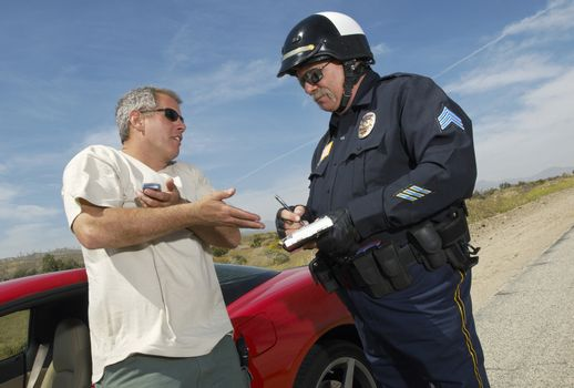 Traffic cop writing a ticket for driver of sports car