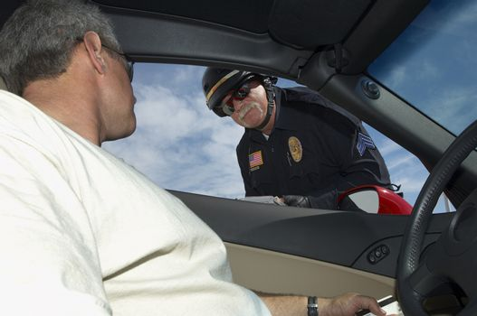 Man in car having discussion with police officer