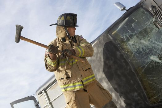 Firefighter breaking the windshield of crashed car with axe