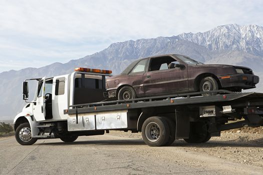 Damaged car being transported on tow truck with mountain range in the background
