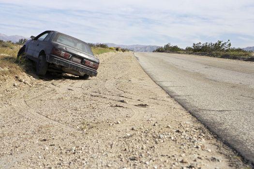Abandoned car on desert road