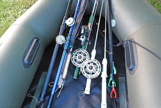 Rods and spinning prepared for fishing, lie in pressurized rubber boat