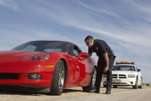 Traffic police officer in discussion with man in red sports car
