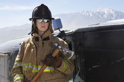 Female firefighter holding axe by a crashed car
