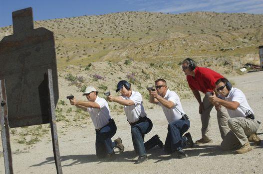 Men firing guns at shooting range