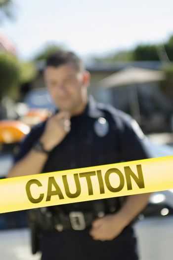 Closeup of a caution tape with male police officer in the background