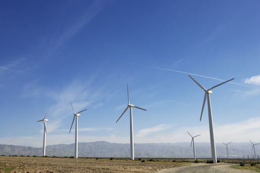 Wind turbines generating electricity in desert against blue sky