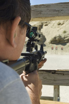 Closeup of a military man aiming rifle at firing range during combat training