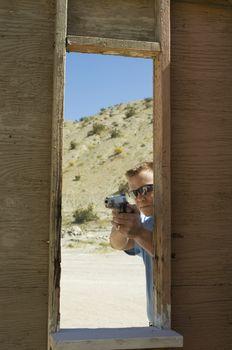 Caucasian man aiming handgun at firing range during combat training