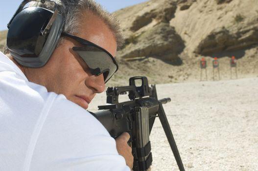 Closeup of a man aiming machine gun at firing range